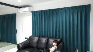 白い壁面と黒いソファに調和するカーテン